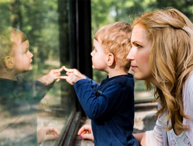 Side View of Toddler and Mother In Front of Safety Glass