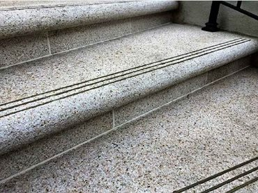 Radial stair treads and risers were handcrafted from Golden Dune Granite
