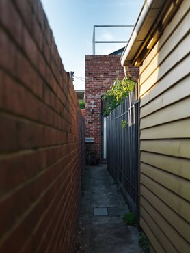 Narrow walkway between buildings to enter Gezellig House. Photography by Trevor Mein
