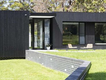 The new residence is a low profile, charred timber and glass façade creation