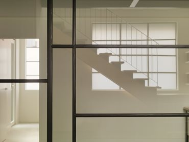 Passive Warehouse view of stair through day lit interior. Photography by Trevor Mein