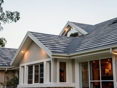 Detailed rooftop image of home with grey concrete roof tiles