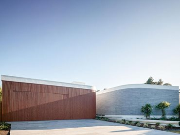The vertical timber look aluminium battens effectively disguise the garage door by effortlessly integrating with the building's sculptural element