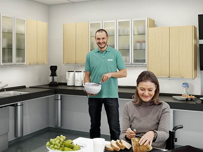 carer and woman in wheelchair cooking together kitchen