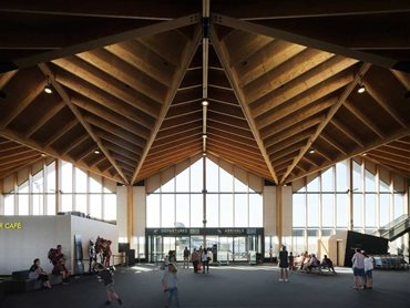 The timber structure forming the roof captivates with natural warmth, texture and scale