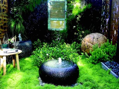 Lush outdoor garden with large round water feature