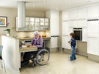 elderly woman in wheelchair cooking with grandson in accessible residential kitchen