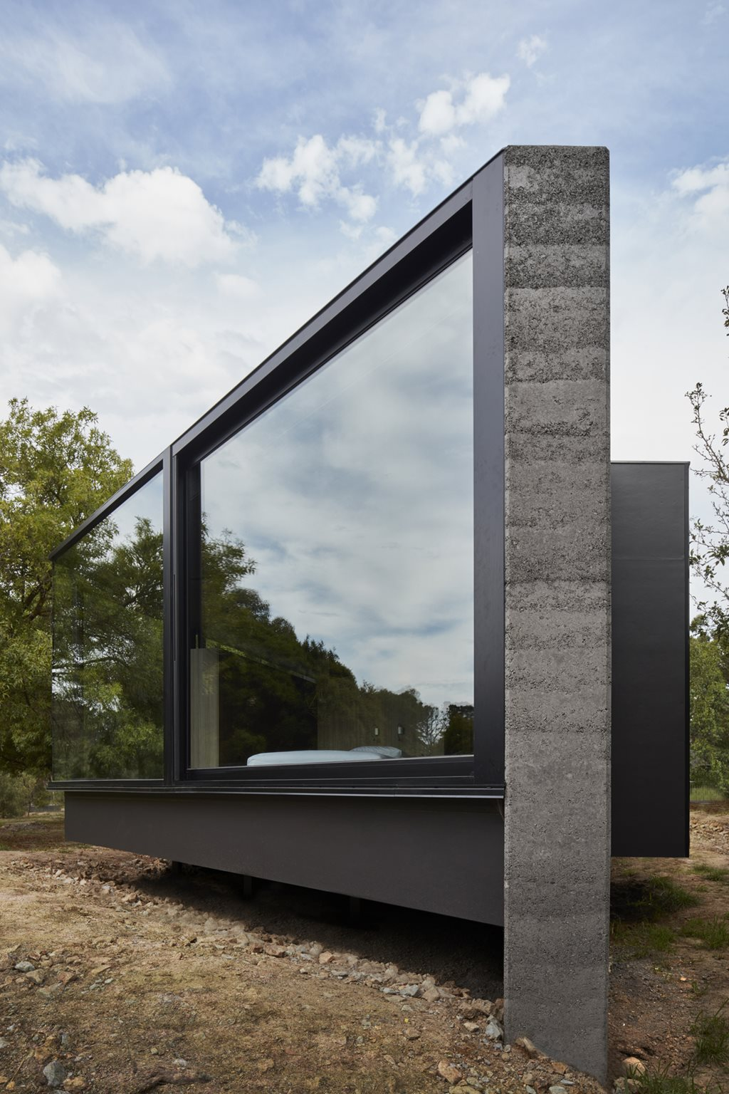 Rammed Earth Addition Slots Between Existing Trees Linking
