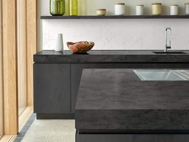 Interior of modern kitchen with dark gray solid bench surface