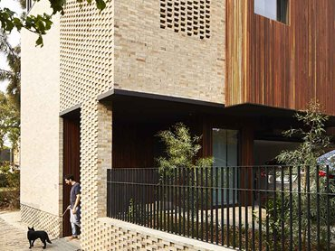 The natural earthy hues of the timber and brickwork are stitched together by a handful of darker building elements, balustrade rails and external louvres