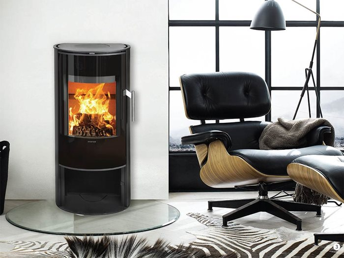 Black Castworks cast iron Danish wood fire heater in living room with floor to ceiling window
