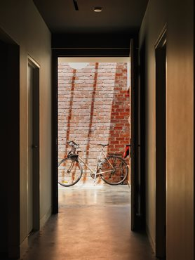 Bicycle in light filled brick atrium, entry to Gezellig House. Photography by Trevor Mein