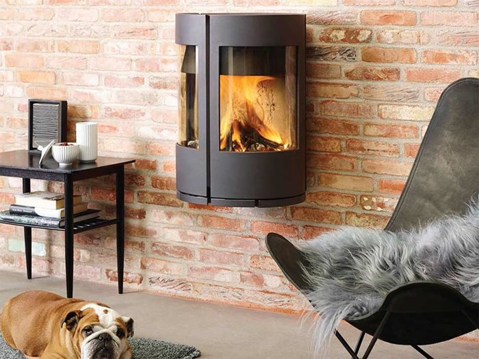 Castworks cast iron Danish wood fire heater installed onto brick wall in living room