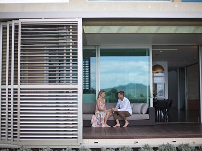 LouvreTec White Shutters on House Exterior With Couple Sitting on Couch