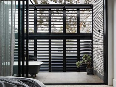 Petersen bricks are paired with aluminium plantation shutters for shading and privacy throughout the top storey