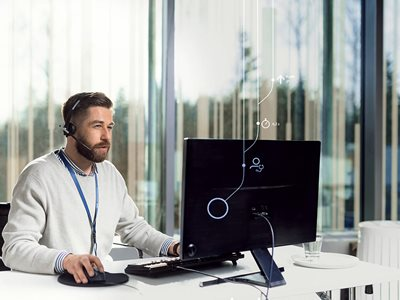 Kone Customer Care Center Operator with Headset in Front of Computer