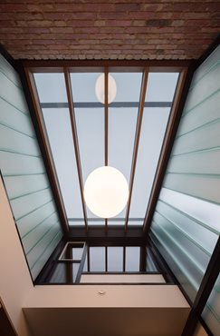 Channel glass atrium and skylight. Entry into Gezellig House. Photography by Trevor Mein