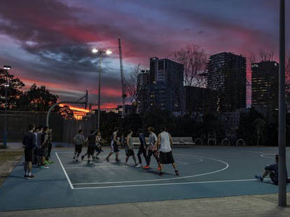 A group of young Asian men play basketball in the evening at Prince Alfred Park, Sydney. Image: icsnaps/Shutterstock