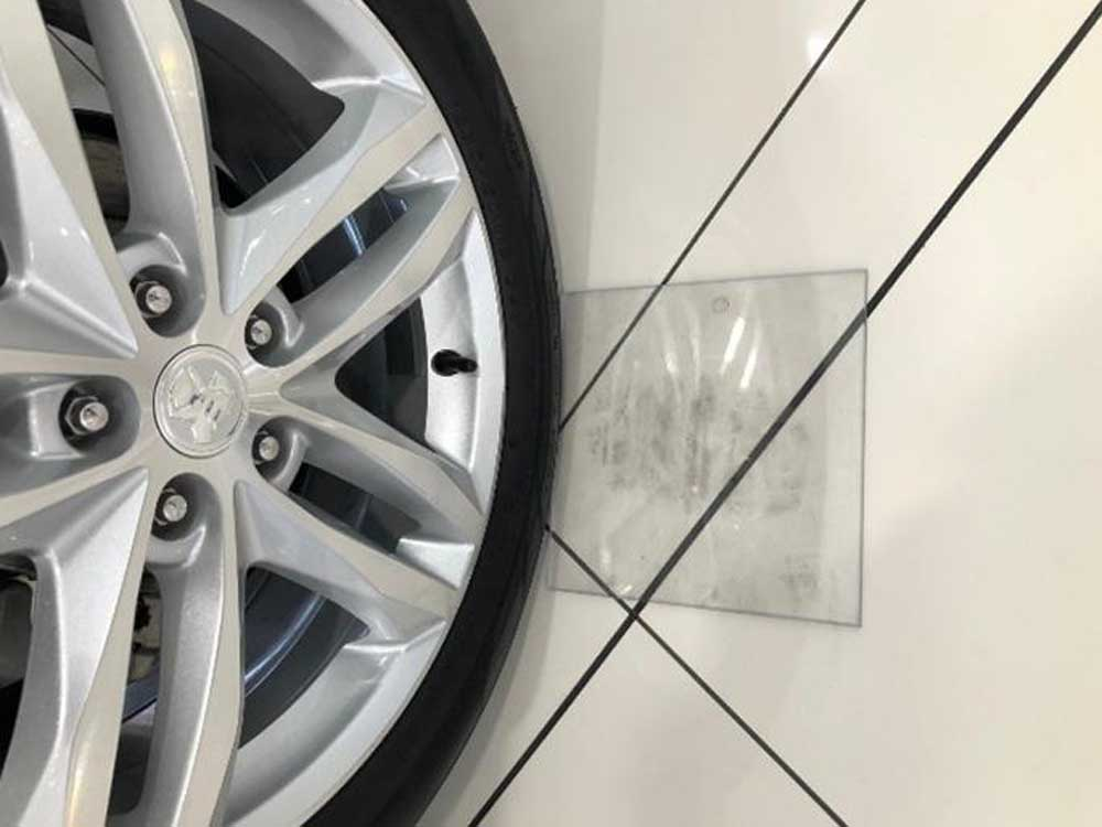 Polycarbonate pads protect car showroom floors from black tyre markings