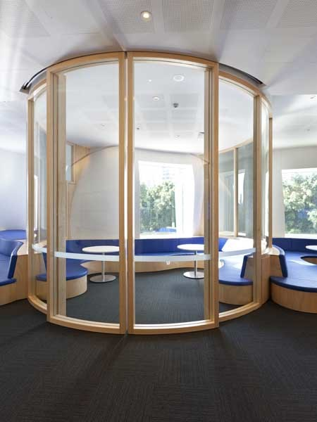 Large format curved glass bi-sliding doors welcome visitors to the area