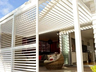 Outdoor room with large white shutters