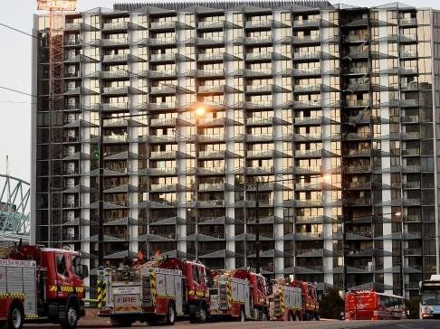 Firefighters at the apartment block the morning after the fire. Photography by Nicole Garmston/Image: Herald Sun