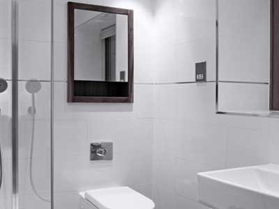 A bathroom featuring white wall tiles